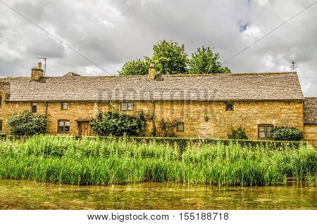 View across the River Eye to historic terraced cottages at Lower Slaughter in the English Cotswolds.