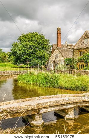 Footbridge over River Eye at Lower Slaughter in the English Cotswolds, with historic houses and watermill in the background.