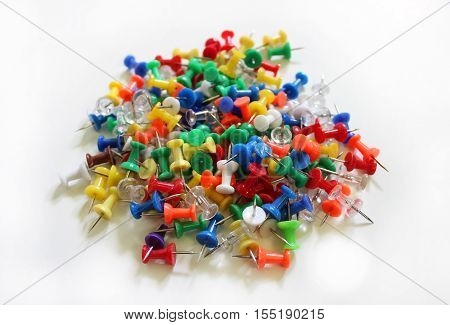 A heap of colorful thumb tacks against a white background.