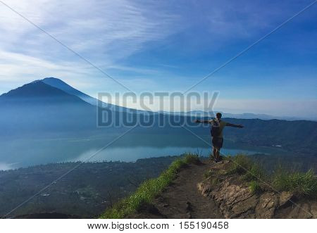 Man on the top of the mountain path. Beautiful morning landscape with distant volcano, volcanic lake, sea, sky with fluffy clouds. Tropical island vacation. Wanderlust poster or banner template