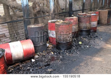 KOLKATA, INDIA - FEBRUARY 10: Old rusty barrel left in the road leaking thick black tar or oil on an urban street in Kolkata, India on February 10, 2016.