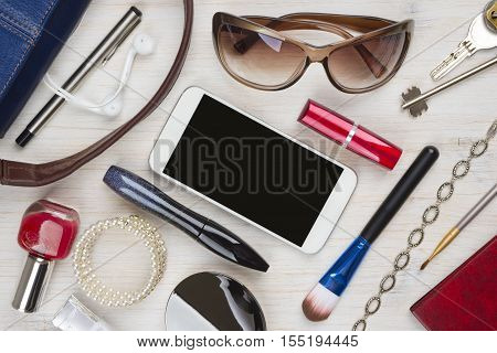 Top view of women bag stuff on wooden texture background
