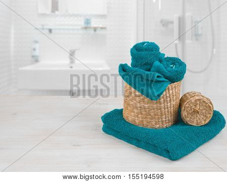 Turquoise spa towels and wicker baskets on defocused bathroom interior