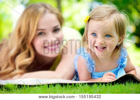 Young Mother With Little Daughter Reading Book In Park