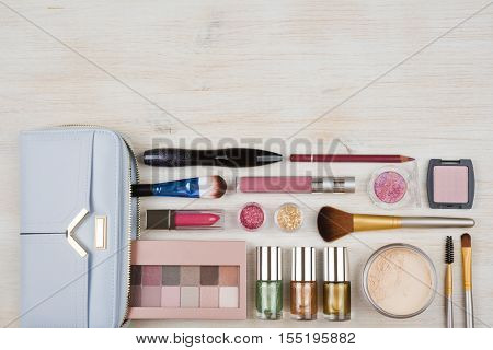 Various makeup cosmetics products on wooden table background with copyspace
