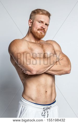 young caucasian muscular bearded man isolated on studio background