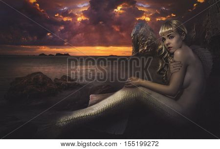 mermaid stranded on a cliff of rocks at sunset, creative image and fantasy