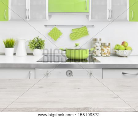 Wooden table on green modern kitchen bench interior background