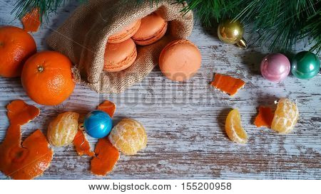 Orange macaroons in jute sack and Christmas tree decorations on old wooden background