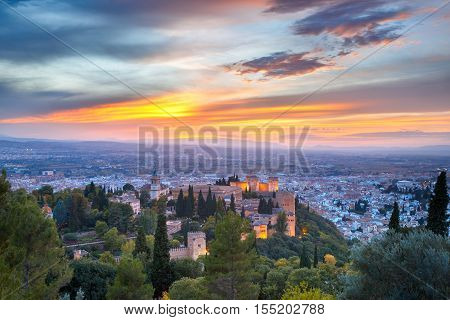 Palace and fortress complex Alhambra with Iglesia de Santa Maria, Palacios Nazaries and Alcazaba during sunset in Granada, Andalusia, Spain