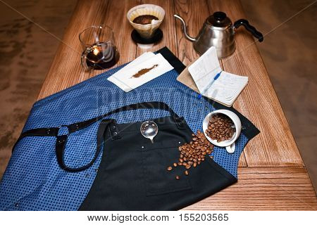 Barista apron on the table in cafe with various stuff for alternative coffee brewing. Product photography. Coffee preparation service concept