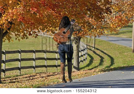 Back view of brunette woman walking away with guitar in the fall season