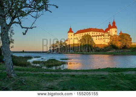 LIDKOPING, SWEDEN - OCTOBER 5 2016: Late autumn afternoon by Lake Vanern and Lacko Castle. Lacko Castle is considered as one of the most beautiful castles in Sweden.