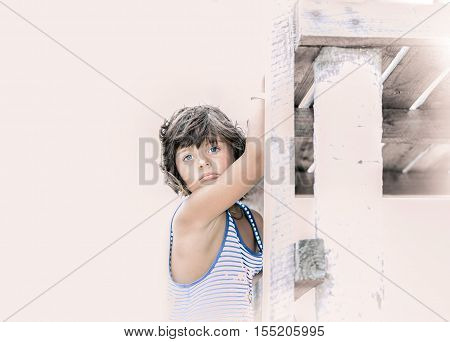 amazing portrait of a tired bored little beautiful girl holding wooden deck against light pinkish white background