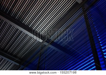 Colorful Jalousie shutters louvers over windows, gray and blue light