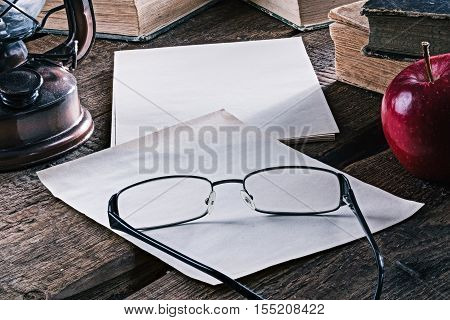 Desk with paper sheets, books, lamp, red apple and eyeglasses on the rustic wood table