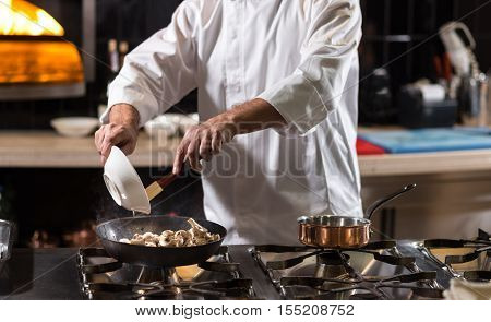 Preparing ingredients. Concentrated involved hardworking chef frying mushrooms on the frying pan while standing near the stove in the kitchen of the restaurant and cooking