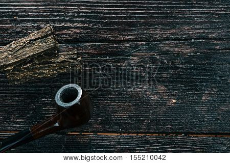 Smoking pipe and tobacco flake on the wooden surface. Flat lay. Selective focus