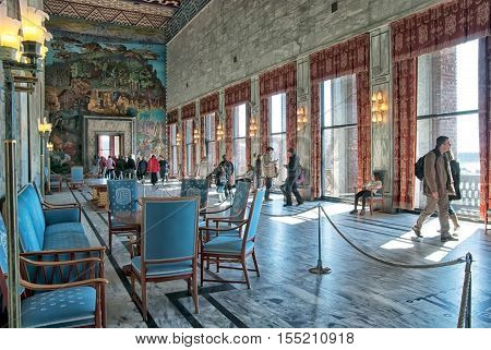 OSLO, NORWAY - APRIL 12, 2010: The City Hall Building interior. People in The Gallery of Celebration with fresco by Axel Revold, tapestry by painter Kare Jonsborg, weaver Else Halling.