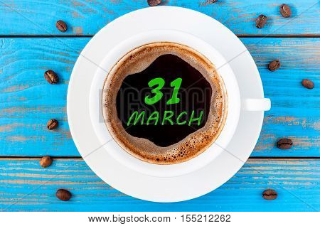 March 31st. Day 31 of month, calendar written on morning coffee cup at blue wooden background. Spring time, Top view.