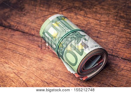 Euro banknotes. Euro currency. Euro money. Close-up Of A Rolled Euro Banknotes On concrete or Wooden table.