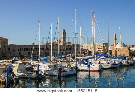 Port Of Acre, Israel. With Boats Mosque And The Old City In The Background.