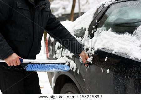 Winter snow vehicle. Man cleaning car from snow with the help of special brushes.