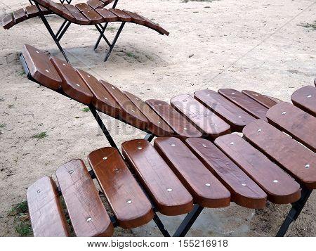 The wooden sunbeds on the sandy beach
