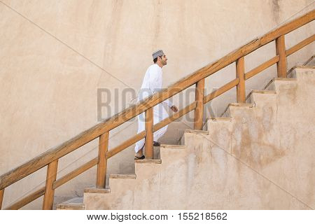 Omani Man Walking Up The Stairs In Nizwa Fort