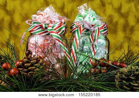 glass jars full of red and green Christmas candy and holiday pine garland