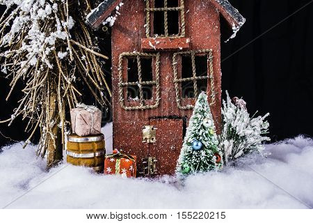 arts and crafts scene of rustic house in deep snow with Christmas tree, and gifts