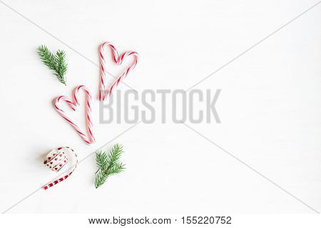 Christmas composition. Christmas candy canes and fir branches. Flat lay top view