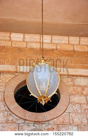 Old fashioned lamp in Bahai world center painted in gold with Haifa reflection
