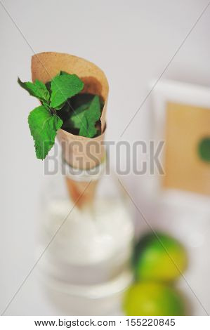 Wilting bouquet of mint leaves lime water bottle - set of ingredients for lemonade partial blur.