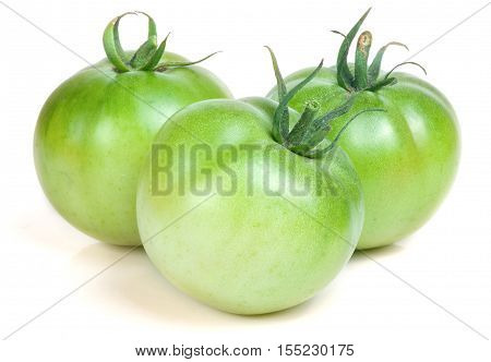 Three green unripe tomato isolated on white background.