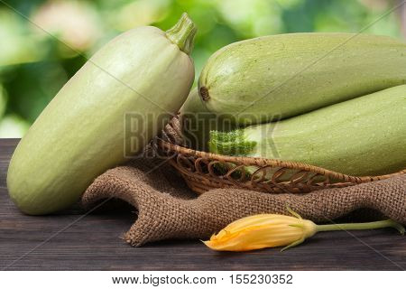 three courgettes with a flower on sackcloth and wooden background.