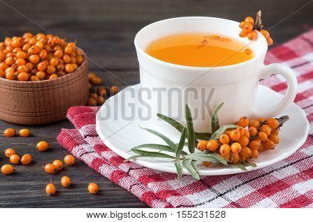 Tea of sea-buckthorn berries with branch on dark wooden background.