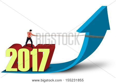 Image of young businessman pulling up a growth arrow with a rope while standing above numbers 2017