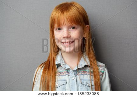 Portrait of a cute ginger girl with freckles gray background