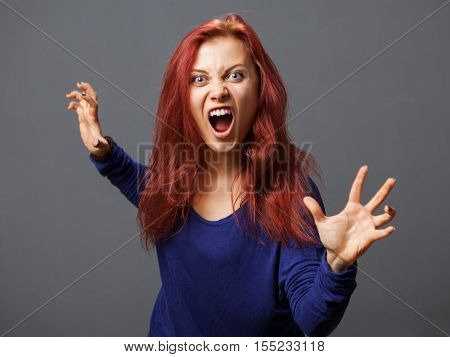 Young furious woman with opened mouth gray background