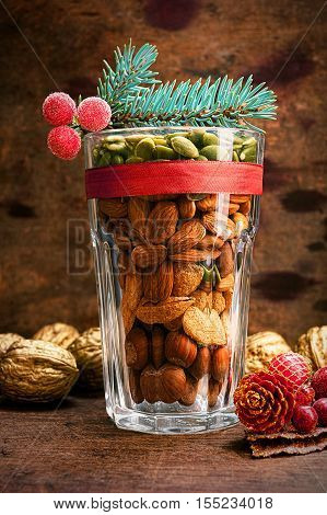 Christmas decoration glass with a variety of nuts on a wooden background