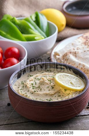 Humus in homemade bowl chapati and vegetable.