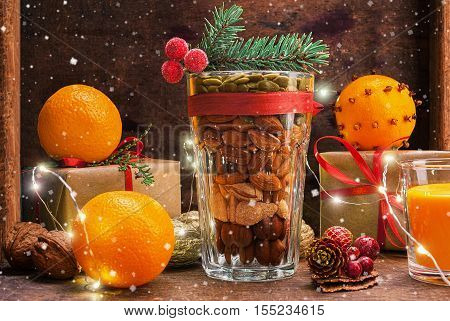 Christmas decoration glass with a variety of nuts on a wooden background with flying snow