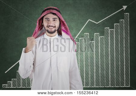 Image of a successful middle eastern businessman celebrate his success with financial graph on the blackboard