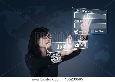 Young Asian businesswoman finding jobs online in the virtual website on futuristic screen. Concept of online job searching
