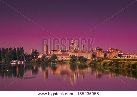 Panoramic view of enchanted Mantua city at sunset reflecting on the Mincio river