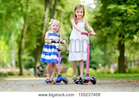 Two Adorable Little Sisters Riding Their Scooters In A Summer Park