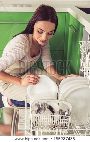 Beautiful young woman in apron is putting dishes into dishwasher and smiling while washing dishes in kitchen