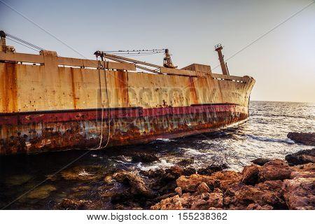 Seascape: boat  shipwrecked near the rocky shor. Mediterranean, near Paphos. Cyprus