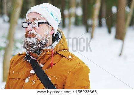 A young bearded man in a cap and jacket during a snowstorm in the woods face and beard covered with snow glasses plastered with snowflakes